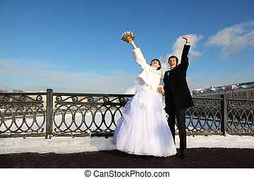 happy groom and bride shouting and waving their hands at...