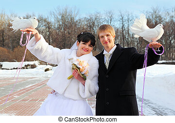 smiling beautiful bride and groom hold white doves at winter...