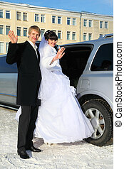 smiling groom and bride stand near wedding limousine, waving their arms and sit down in car at winter outdoors