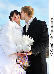 beautiful bride and groom hold pair of white doves at winter...