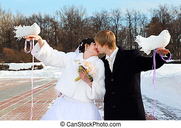 beautiful bride and groom hold white doves and kiss at...