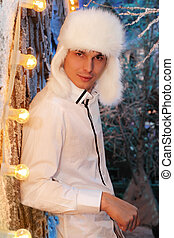 Young man wearing white shirt and white fur hat stands near...