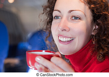 Young woman drinks coffee from the red cup on the airplane, shallow depth of focus.