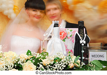 Bottles of champagne wine dressed in wedding gowns stand on festive table with flowers; Blurred faces of bride and groom in background