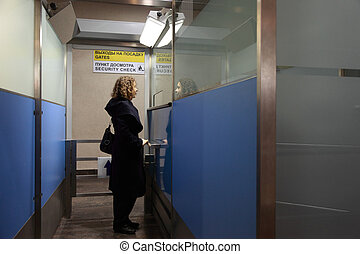 Young woman stands in the security checkpoint at the airport. Shot in all growth.