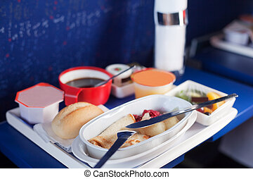 Tray of food on the plane. Focus on a plastic cruet stand...