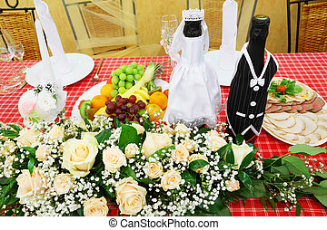 Bottles of champagne wine dressed in wedding gowns stand on festive table with food and flowers