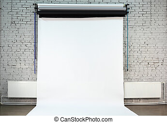 White background on white brick wall inside studio owned by...