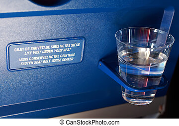 Plastic cup with water in the holder on airplane.