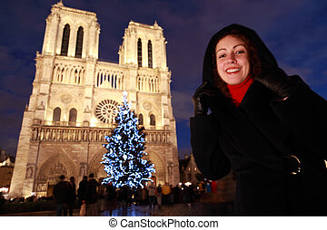 Young smiling woman stands on the square in front of Notre...