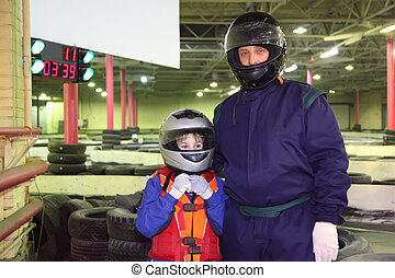 little boy and his carting trainer are standing in helmets; ground for carting