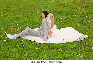 Beautiful young groom and bride wearing white dress sitting back to back on green grass and holding hands