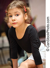 little girl in ballet class sits on string on floor and...