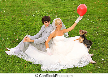Beautiful young groom and bride wearing white dress sitting on green grass; bride play with small dog and red balloon