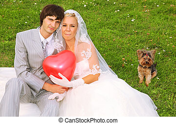 Beautiful young groom and bride wearing white dress sitting on green grass and keep red balloon heart; small dog sits near pair