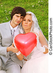 Beautiful young groom and bride wearing white dress sitting on green grass, keep red balloon heart and look at camera