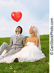 Beautiful young groom and bride wearing white dress sitting on green grass and looking at flight of heart-shaped red balloon