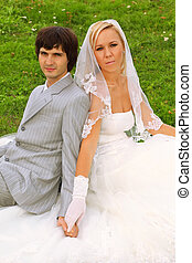 Beautiful young groom and bride wearing white dress sitting on green grass and holding hands