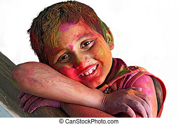Close up face of young boy playing Holi, smiling with...