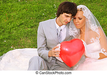 Beautiful young groom and bride wearing white dress sitting on green grass, keep red balloon heart and look at balloon