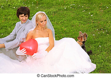 Beautiful young groom and bride wearing white dress sitting on green grass; bride keeps red balloon heart; small dog looks on balloon