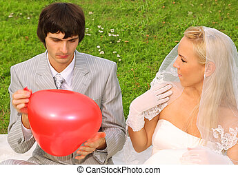 Beautiful young groom and bride wearing white dress sitting on green grass, groom keeps red balloon heart and bride looks at groom