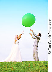 Beautiful young groom and bride wearing white dress stand on green field and throws in sky big green balloon