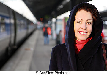 Young smiling woman close-up stands on the railway platform.