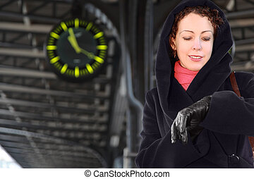 Young woman looks at her wristwatch, standing on the railway platform.