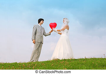 Beautiful young groom and bride wearing white dress stand on green field and keep heart-shaped red balloon