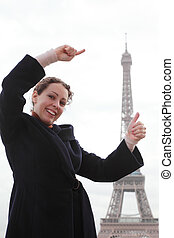 Smiling young woman shows with her hands how high the Eiffel Tower, standing on its background.