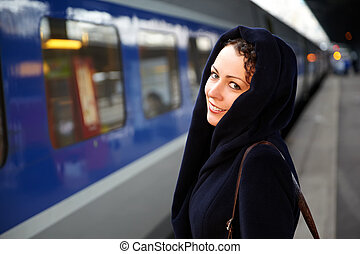 Young smiling woman close-up stands on the platform near the train.