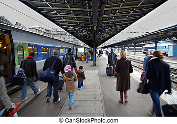 Passengers from the arrived train go by the platform