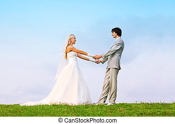 Beautiful young groom and bride wearing white dress standing on green grass and holding hands