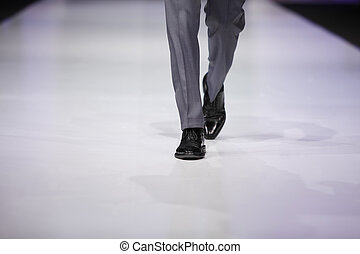 foot of male model in gray trousers and black shoes on...