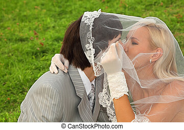 Beautiful young groom and bride wearing white dress hidden...