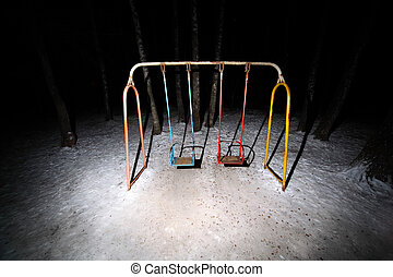 Old rusty swing stand in dark park at winter night; white...