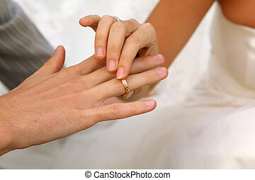 bride wears wedding gold ring groom. only their hands in...