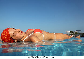 beautiful young woman in red swimsuit sunbathing in water in...