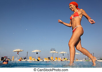 beautiful young woman in red swimsuit runs and dives into blue, clear water of pool. in background beach umbrellas. from the underwater package