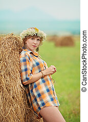 Pretty farm lady near a haystack