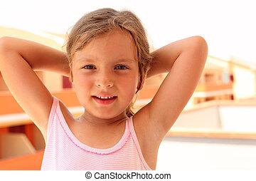 little girl in pink singlet put her hands behind head. in...