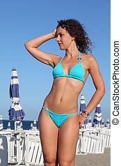 beautiful young woman in blue swimsuit stands on beach, rows...