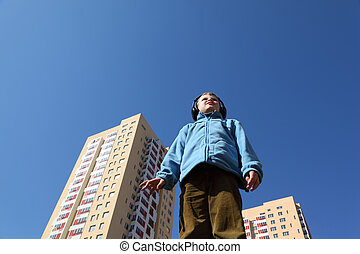 little boy in blue jacket and headphones worth it, two yellow blocks of flats