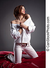 Sexy woman posing in white shirt and jeans