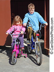 little brother and sister ride children's bicycles. girl in...