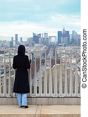 young woman standing on Triumfaly arch and looking at La...