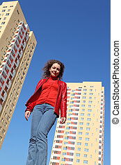 beautiful young woman in red jacket and blue jeans smiling....