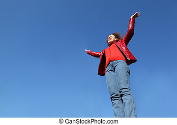 beautiful young woman in red jacket and blue jeans raises his hands to sky