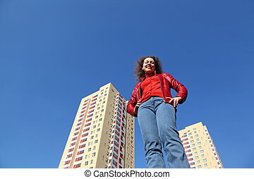 beautiful young woman in red jacket and blue jeans smiling. in background two multi-story yellow house